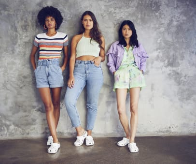 Three models posing with white clogs.
