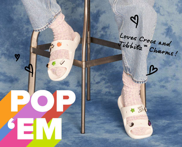 Model posing with White Sandals with Jibbitz - image text reads 'Pop 'Em' & 'Loves Crocs and Jibbitz Charms'