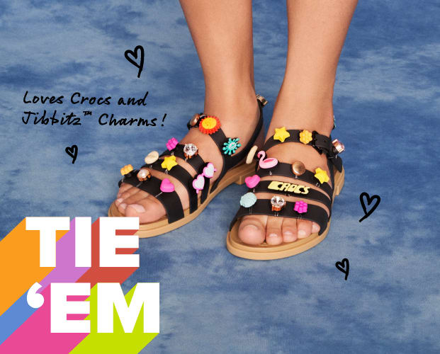 Model posing with Black Strappy Sandals with Jibbitz - image text reads 'Tie 'Em' & 'Loves Crocs and Jibbitz Charms'