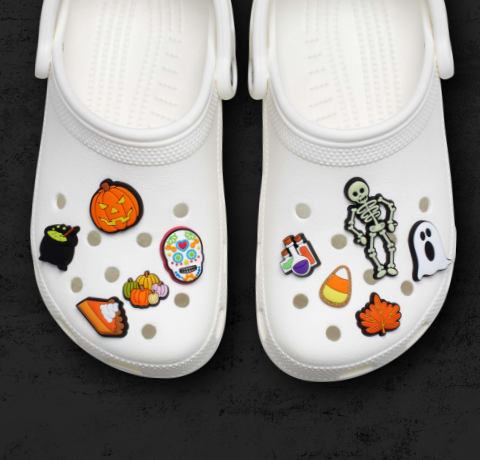 Halloween-themed Jibbitz charms on a pair of white clogs.