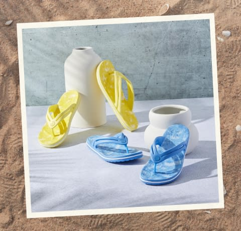 Yellow and Blue Flip Flops next to White Ceramic Vase and Bowl